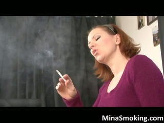 sexy brunette hair chick smokes a cigarette