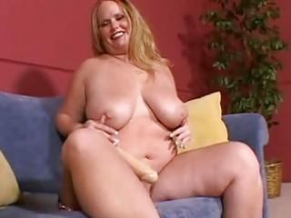 large breasted blonde milf masturbates on the sofa